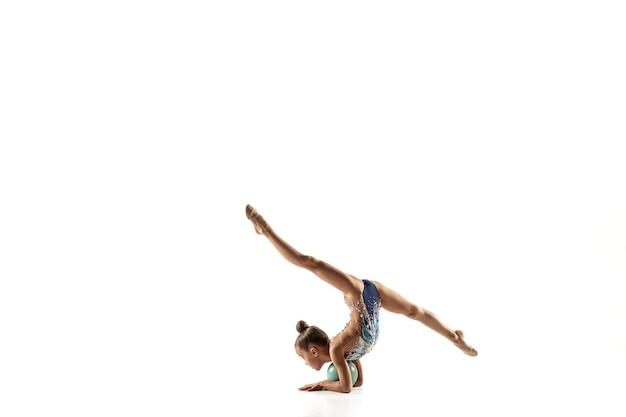 Little gymnast girl isolated on white studio wall.