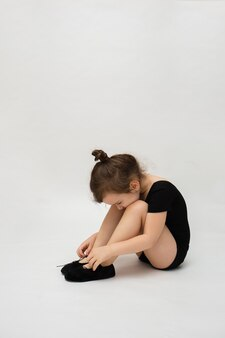 Little gymnast girl sits on a white background