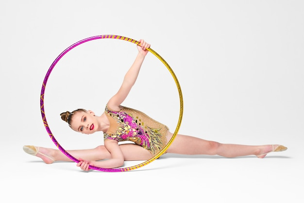 Маленькая гимнастка в купальнике с пайетками выполняет упражнение с обручем на белом фоне