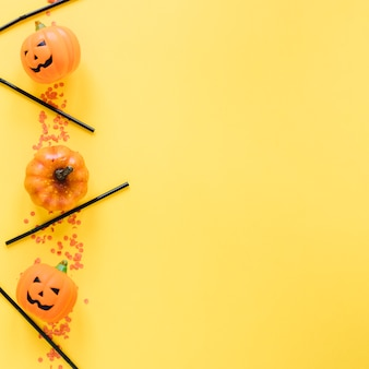 Little halloween pumpkins and plastic tubes laid in line