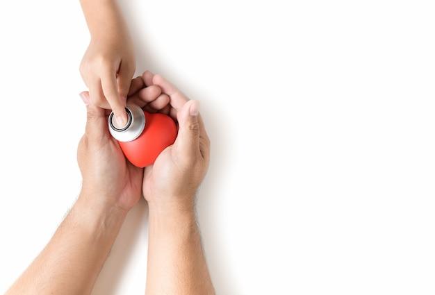 赤いハートをチェックする聴診器を持っている小さな手
