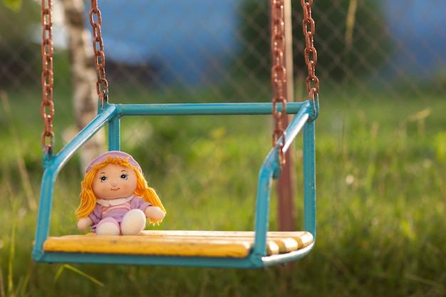 Little hand made doll seating on yellow wooden bench in bright summer day