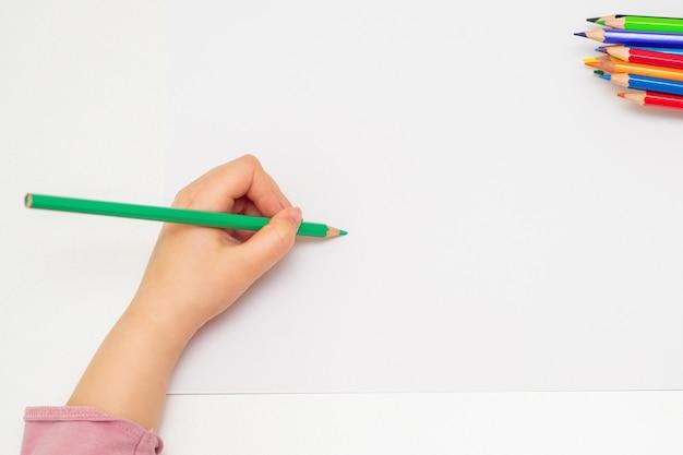 Маленькая рука девушки, рисование на бумаге