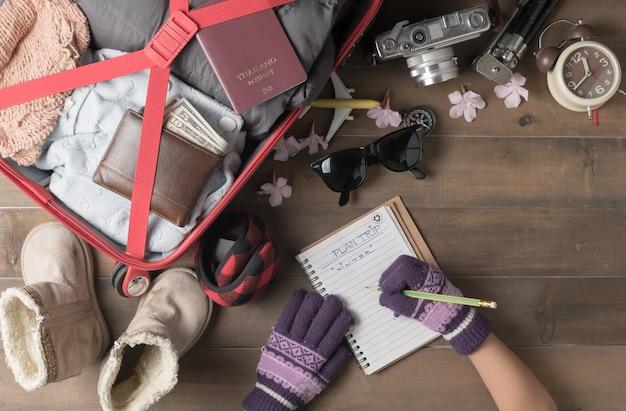 小さな手は、古い木製ボード、フラットレイのためのアクセサリー旅行アイテムと冬の旅行計画を書く