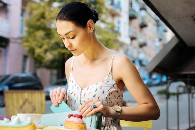 小さなハンドバッグ。カフェでデザートを食べる前にハンドバッグに入れながらスマホをじっと見つめる落ち着いた真面目な女性