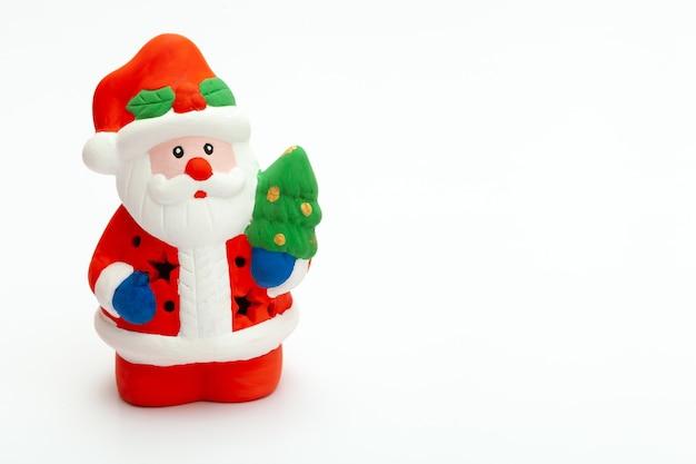 작은 수제 장난감 산타클로스는 흰색 배경에 서 있습니다. 크리스마스와 새 해 개념입니다. 디자인에 대 한 흰색 배경에 고립