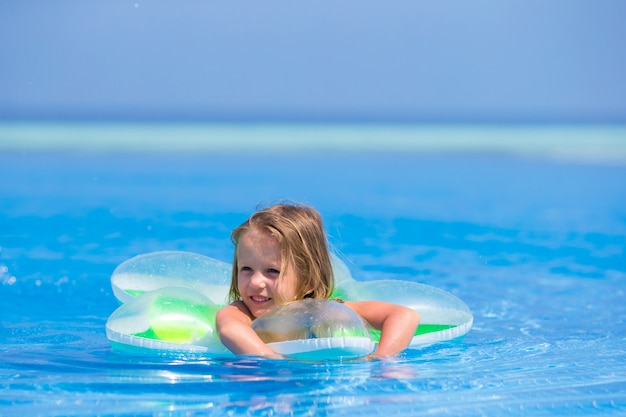 Little happy adorable girl in outdoor swimming pool
