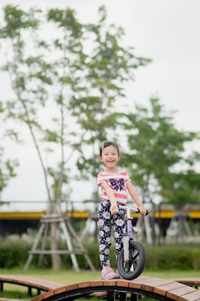Little happy asian child girl ride bike at playground