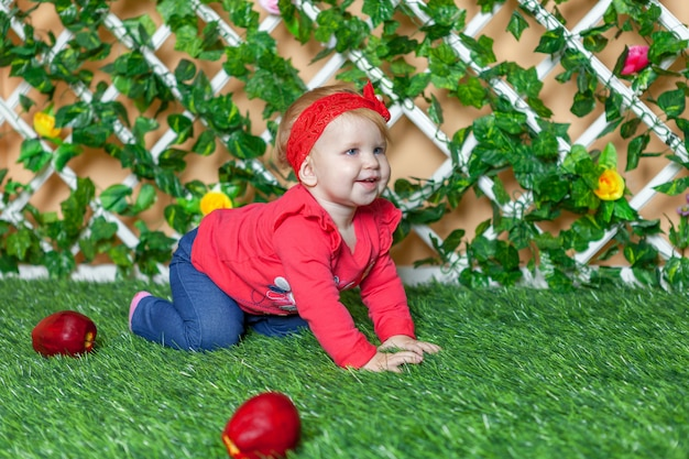 Little happy baby girl crawling on the grass in the park and smiling