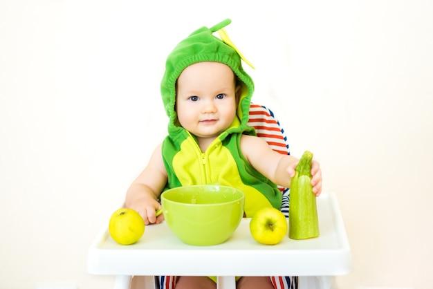スプーンで小さな幸せな赤ちゃんはハイチェアに座って、皿の上のお粥を食べる