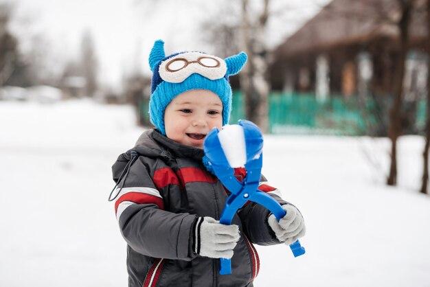 冬に雪玉を遊んで幸せな男の子