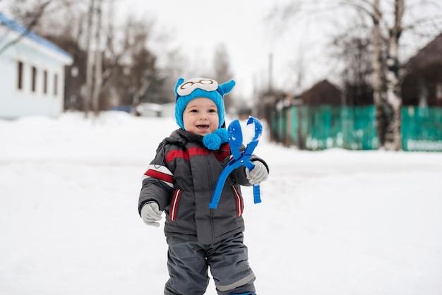 Little happy boy child playing snowballs in winter