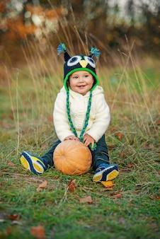 Маленький счастливый мальчик в вязаной шапке сидит с тыквой на траве среди осенних деревьев на фоне и осенних листьев в земле