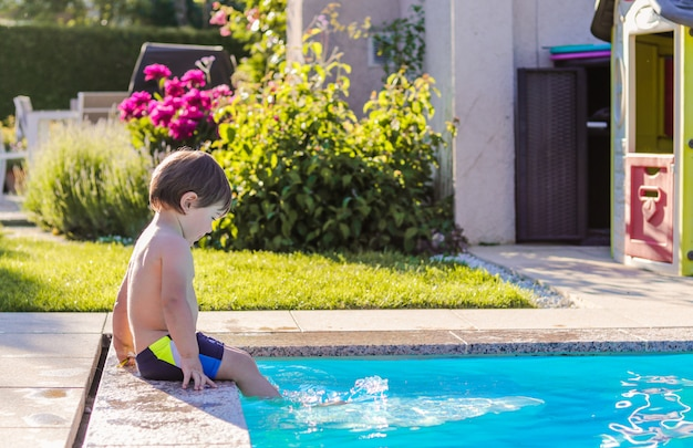 Little happy boy sitting on side of swimming pool in garden playing by his feet in water having fun.