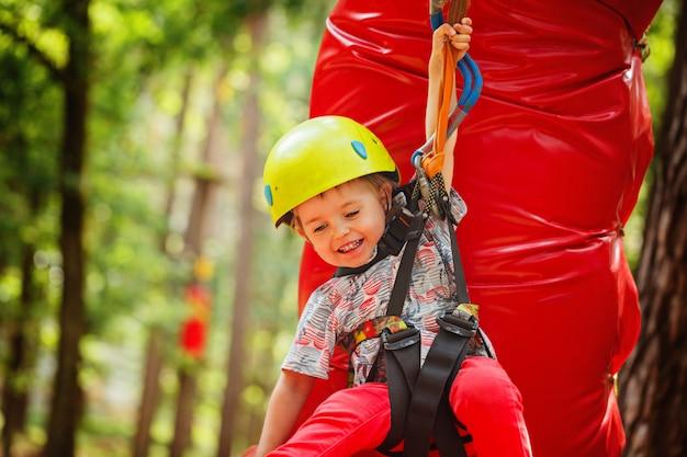 Little happy child boy in adventure park in safety equipment in summer day