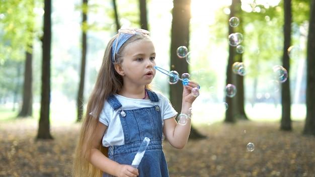 緑豊かな公園の外でシャボン玉を吹く小さな幸せな子の女の子。屋外の夏の活動の概念。