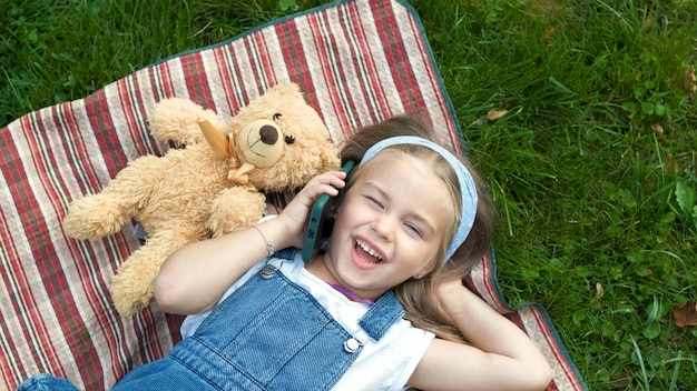 Little happy child girl laying on a blanket on green lawn in summer with her teddy bear talking on mobile phone.