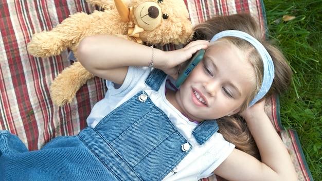 携帯電話で話している夏の緑の芝生の毛布の上に横たわっている小さな幸せな子供の女の子。