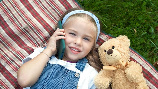 彼女のテディベアが携帯電話で話している夏に緑の芝生の毛布の上に横たわっている小さな幸せな子供の女の子。