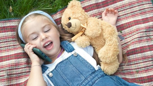 携帯電話で話している彼女のテディベアと緑の芝生の上に横たわっている小さな幸せな子供の女の子。