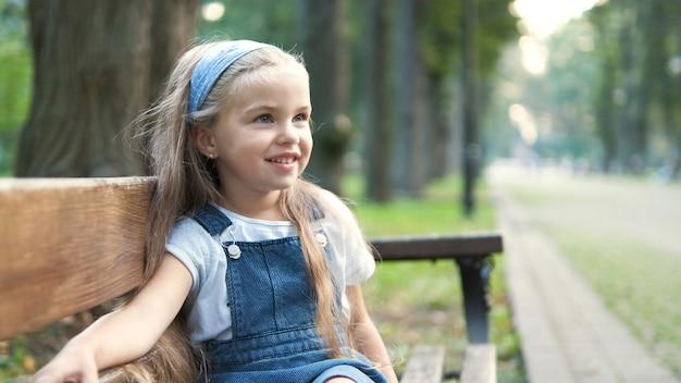 夏の公園で幸せそうに笑っているベンチに座っている小さな幸せな子の女の子。