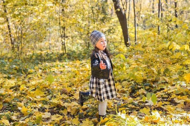 Little happy child girl walking in the autumn park