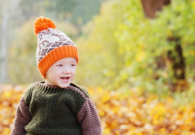 Маленький счастливый ребенок в осеннем парке
