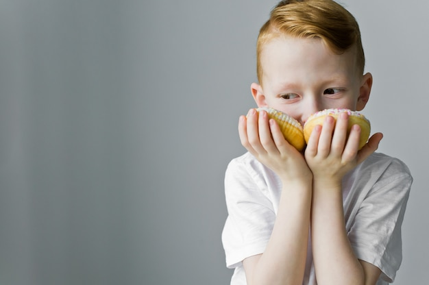 Little happy cute boy is eating donut on grey background wall.