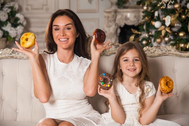 クラシックインテリアで飾られたクリスマスツリーを背景に楽しんで、ドーナツを食べて美しい若い母親と小さな幸せなかわいい女の子。新年のお祝いの夜に幸せな家族。