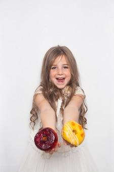 小さな幸せなかわいい就学前の女の子は白でカラフルなドーナツを食べています