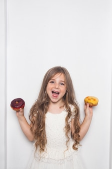 Little happy cute preschool girl is eating colourful donuts on white background isolated.