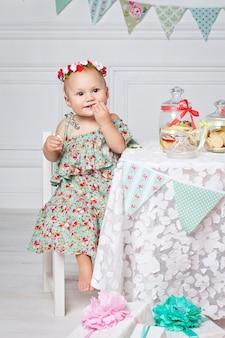 最初の誕生日を祝う小さな幸せな女の子。キャンディーバーでテーブルに座っているかわいい女の赤ちゃん