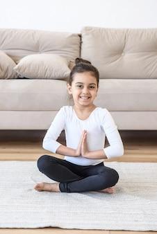 Маленькая счастливая девочка в позе лотоса тренировки дома