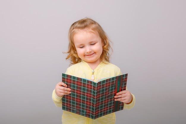 Little happy girl child surprised with a book in her hands isolated on a gray background.concept of education