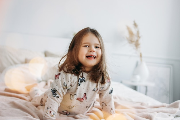 Little happy girl in cozy pajamas on parents bed in home