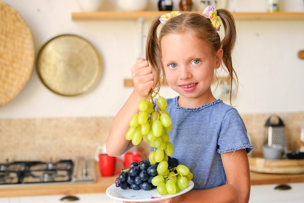 朝食を食べて、果物の陽気な子供とお茶を飲む小さな幸せな女の子