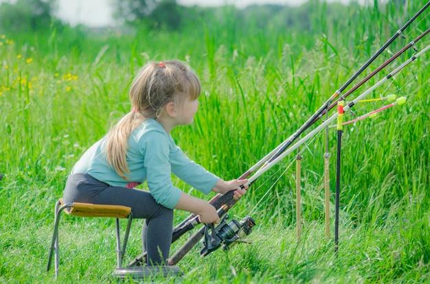 森の川の近くの釣り少し幸せな女の子