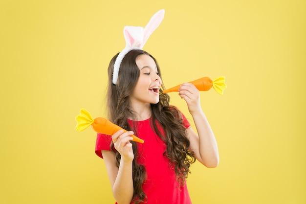 토끼를 위한 작은 행복한 소녀 음식. 건강한 어린 시절. 치아에 좋습니다. 토끼처럼 당근을 갉아먹습니다. 토끼 귀에 아이는 당근을 먹는 것을 좋아합니다. 당근과 아이 토끼 의상.