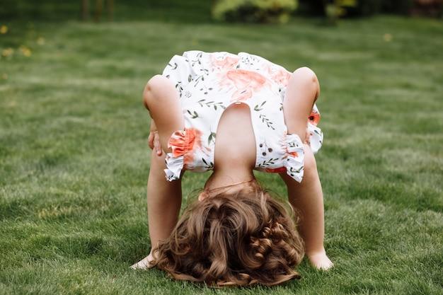 緑の夏の公園で楽しんでいる小さな幸せな女の子