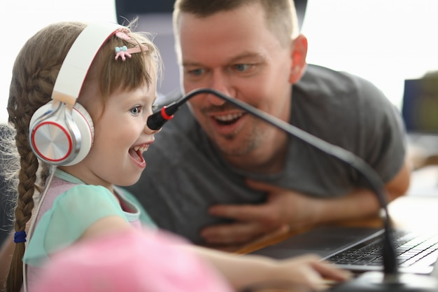 Little happy girl in headphones looks with enthusiasm at monitor next to man