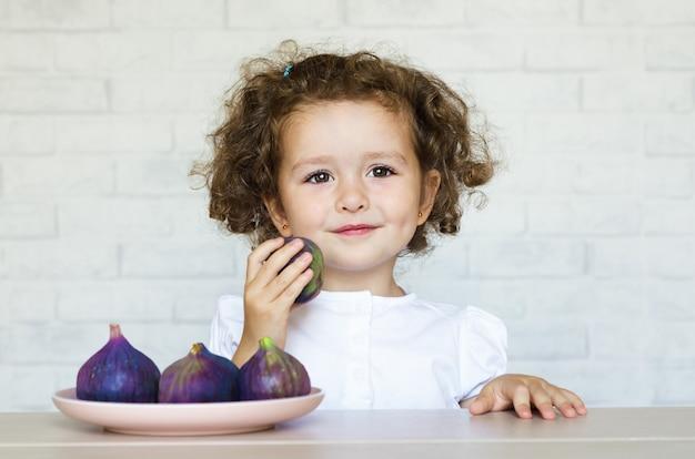 Маленькая счастливая девочка держит инжир