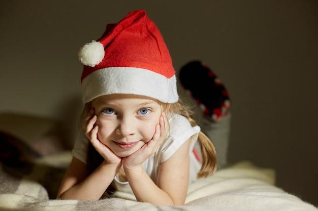 Маленькая счастливая девочка в шляпе санта-клауса ждет рождественских подарков, портрет девушки, ребенок смотрит в объектив камеры