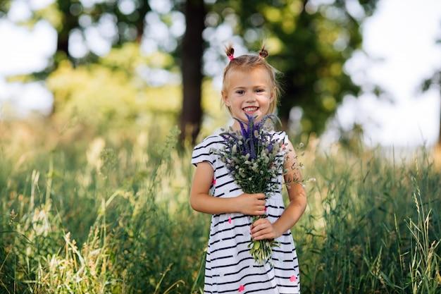 花の花束を持って縞模様のドレスで幸せな少女
