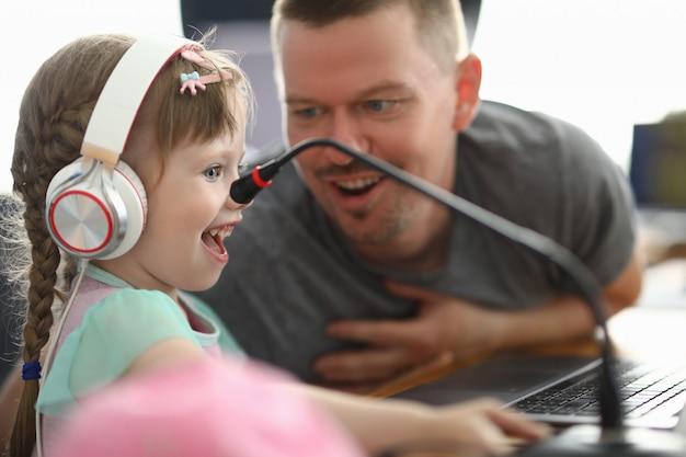 Маленькая счастливая девушка в наушниках смотрит с энтузиазмом на монитор рядом с человеком