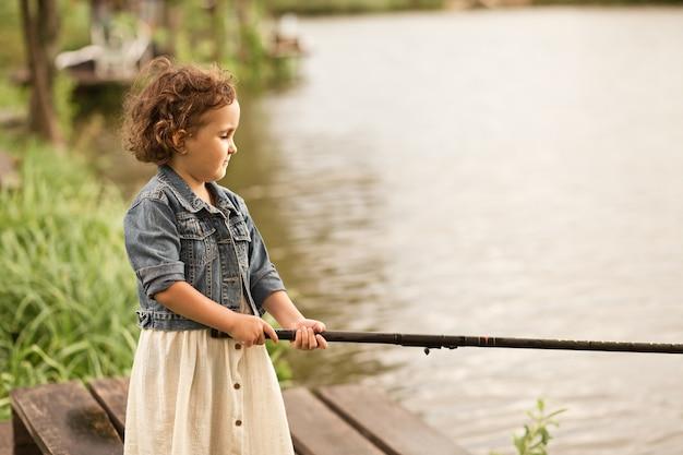 막대로 낚시 하는 마을에서 작은 행복 한 소녀. 여름 시골 생활.