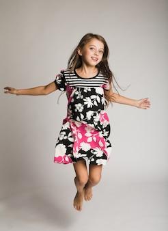Little happy girl jumping of joy