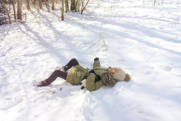 森の新雪の上に横たわっている小さな幸せな女の子。晴れた冬の日。