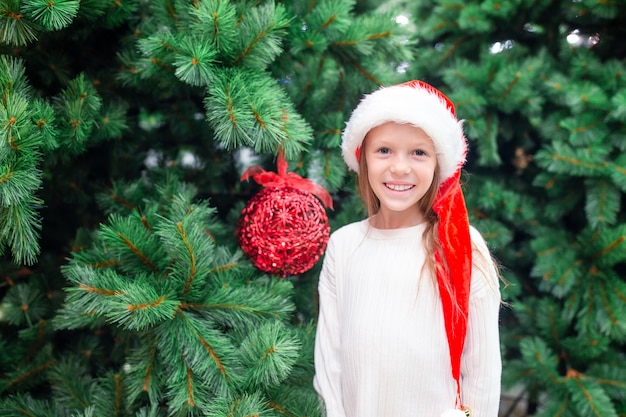 Little happy girl near fir-tree branch in snow for new year.