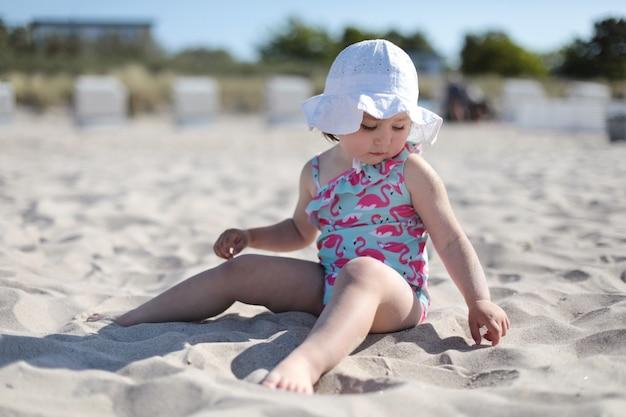 夏と休暇を楽しんでいる白い砂浜の小さな幸せな女の子。