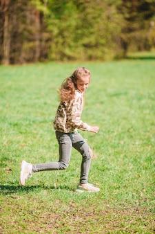 Маленькая счастливая девочка на открытом воздухе в парке работает и веселится